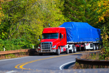 Red semi truck flat bed trailer on winding autumn highway